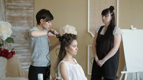Stylisten för makeupkonstnären arbetar med modellen frisören gör utforma för hår av modellen kvinnan arbetar en styler med lager videofilmer