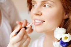 Stylisten gör makeupbruden för bröllopet Arkivbild