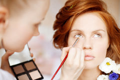 Stylisten gör makeupbruden på bröllopdagen Fotografering för Bildbyråer