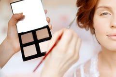 Stylisten gör makeupbruden på bröllopdagen Royaltyfri Fotografi