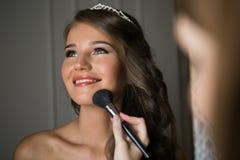 Stylisten gör makeupbruden på bröllopdagen Arkivbild