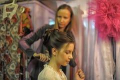 Stylisten gör hår att modellera Fotografering för Bildbyråer