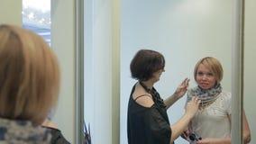 Stylisthjälp som skapar bild med halsduken som är främst av spegeln arkivfilmer