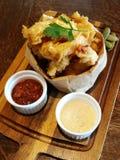 Stylistmat, djup stekt calamari på pappers- påse med serve för chilisås och majonnäs- eller tartarsåspå trämagasinet med suddighe Royaltyfri Bild