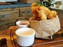 Stylistmat, djup stekt calamari på pappers- påse med serve för chilisås och majonnäs- eller tartarsåspå trämagasinet med suddighe Royaltyfri Fotografi
