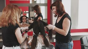 Stylists by hair prepare the hair of a young client of beauty salon for coloring. Adult hairdressers separate the hair into strands in order to make the coloring stock footage