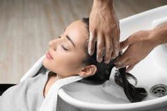 Stylisttvagningklients hår på vasken royaltyfria foton