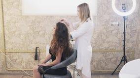 Stylisty makijaż w białej bluzce prostuje jej klienta włosy Gładzi kędziory, patrzeje w lustrze przy rezultatem zbiory