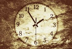 Stylized analog clock. Showing the time on rough brown background stock photography