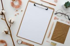 Stylized arranged office accessories clipboard, clips, wristwatch, glasses, cotton flowers, pen all in golden color. Stylized women`s desk, office desk Stock Photography