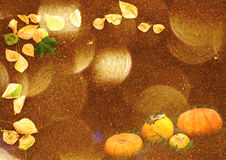 Stylized autumn background with leaves and pumpkins in golden tones Royalty Free Stock Images