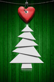 Stylized Christmas Tree on Green Wood Background. White stylized Christmas tree and handmade red wooden heart hanging on a steel cable on green wooden background Stock Photo