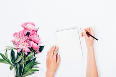 Stylized feminine desk with bouquet of fresh light pink peonies royalty free stock photo