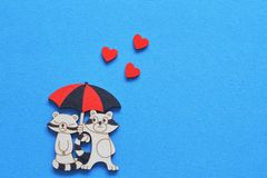 Vintage charming stylized figurine of lovers raccoons under umbrella with red hearts on bright blue background. Minimal background royalty free stock photo