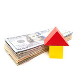 Stylized home next to pile of dollar notes. Stock Images