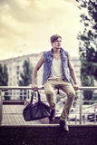 Stylized image of the fashion guy with a bag sitting on the back Royalty Free Stock Photo