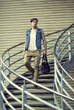 Stylized image of the fashion guy with a bag, walking on stairs Royalty Free Stock Photography