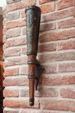 Stylized lamp in the form of the ancient torch on a brick wall. Interior Stock Image