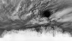 Stylized monochrome landscape of a storm. Stylized negative image of a landscape with clouds forming a massive whirl in the sky Royalty Free Stock Image
