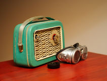 A stylized old radio and motorbike glasses. A old green vacuum tube radio made in Czechoslovakia (early 20th century) and silver vintage motorbike glasses. Both stock photo