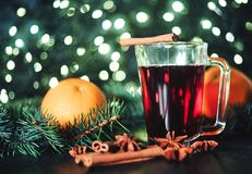 Stylized photo of mulled wine on a christmas background. A mulled wine with orange on a christmas light background Royalty Free Stock Photo