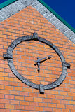 Stylized round clock on brick wall of building façade with coni Stock Photo