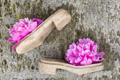 Stylized shoes made of ancient clogs soles and  peony blossoms. Old wooden handmade  soles for  making shoes, footwear fashion, craft  concept Stock Photo