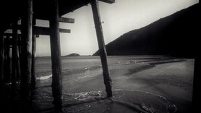 Stylized to look like vintage footage with film grain. A low angle shot from under a pier stock video