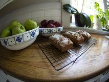 Stylized View of Fresh Baked Loaves of Bread on Wire Cooling Rack, Bowls with Red and Green Apples, Kitchen Window in Background royalty free stock photography