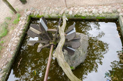 Stylized water mill on stone base of park pond Stock Photography
