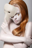 Stylized Woman with Carnival Venetian Mask. Masquerade. Platinum Makeup with Golden Teardrops. Styled Female with Carnival Venetian Mask posing Stock Image