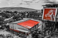 Stylizowana fotografia w czarny i biały z czerwień dachem i koka-koli reklama w mieście Matadi, Demokratyczny Republika Kongo Obrazy Royalty Free