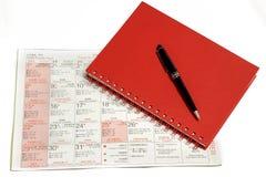 Stylo au-dessus de carnet sur le calendrier de Noël. Photographie stock libre de droits