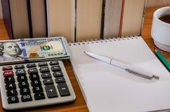 Stylo avec le bloc-notes, les dollars et la calculatrice sur le fond des livres photographie stock