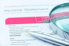 Stylo bille bleu et une loupe sur le rapport des revenus des résultats d'une association Photographie stock libre de droits