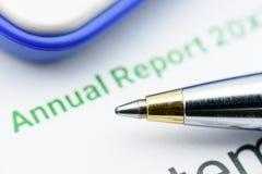 Stylo bille bleu sur le rapport annuel d'une entreprise sur une table Photos stock