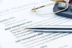 Stylo bille bleu, verres d'oeil et une calculatrice sur un papier des listes de contrôle d'analyse financière Image stock