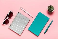 Stylo blanc et vert-bleu, verres, carnet argenté, journal intime bleu vert, cactus sur le fond rose Configuration plate, vue supé Photo libre de droits