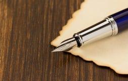 Stylo d'encre et parchemin de papier sur le bois Images libres de droits