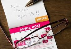Stylo d'or s'étendant sur le calendrier pour le jour d'impôts Photographie stock libre de droits