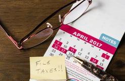Stylo d'or s'étendant sur le calendrier pour le jour d'impôts Photos libres de droits