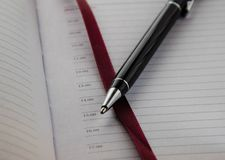 Stylo de stylo à bille sur le fond d'un carnet avec le repère rouge photographie stock libre de droits