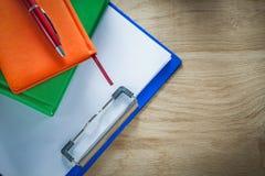 Stylo de biro de bloc-notes de presse-papiers sur le conseil en bois Photo libre de droits