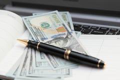 Stylo de boule contre des billets de banque. Images stock