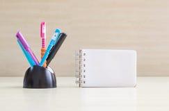 Stylo de couleur de plan rapproché avec le bureau en céramique noir rangé pour le stylo et le page blanc au carnet sur le mur en  Photos libres de droits