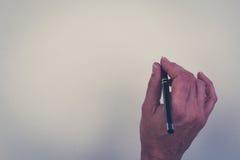 Stylo de participation de main d'isolement au-dessus du fond blanc Photographie stock libre de droits