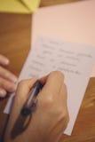 Stylo de participation de main et lettre ou texte femelle humaine d'écriture sur le papier Photos libres de droits