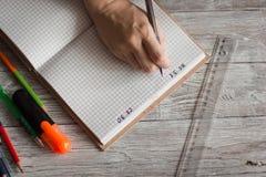 Stylo de participation droitier de femme tout en écrivant sur le petit carnet près de la fenêtre Journaliste indépendant travaill photos stock
