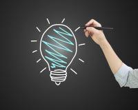 Stylo de participation femelle de main dessinant l'ampoule Image libre de droits