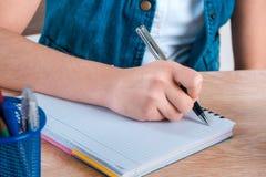 Stylo de participation de main du ` s d'enfant Les lettres d'écriture d'enfant dans un noteboo Photographie stock